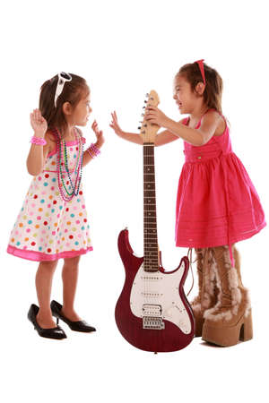 Two adorable sisters playing with guitar