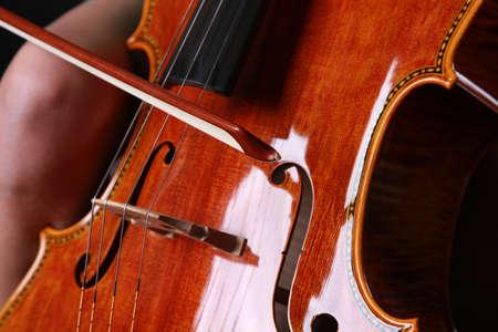 Woman playing Cello on black backdrown photo