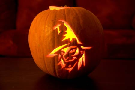 witch face: Pumpkin glowing at night with a witch face Stock Photo