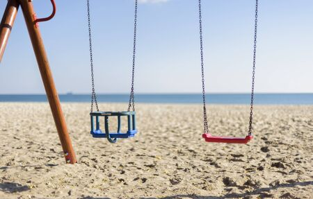 two empty kid swings on the Beach in a sunny day