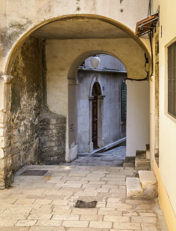 Empty street with arch in the city of Sibenik, Croatia