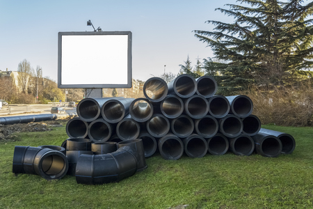 stack of PVC water pipes on a construction site, place for text , ad Space.