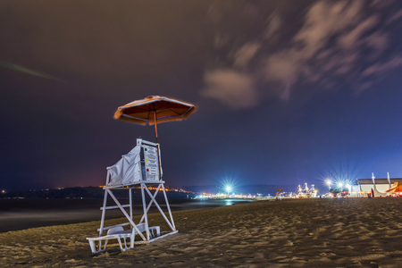 lifeguard chair in a beach by night covered by a umbrella