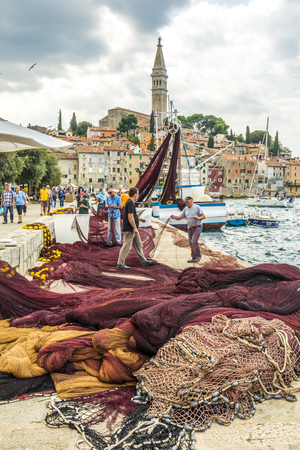 ROVINIJ, CROATIA, SEPTEMBER 27, 2017: Fisher in on the dock are repairing their fishing net in the Middle of tourist in Rovinj