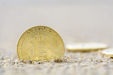 Bitcoins close up on the beach, golden color