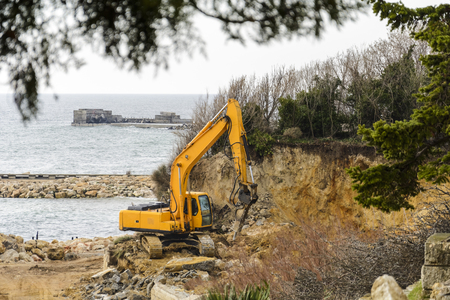 Excavator destroying a beach and a cliff for a hotel construction