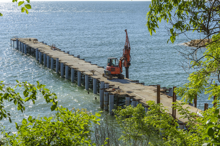 Drilling machine on a pier working, surrounded by water
