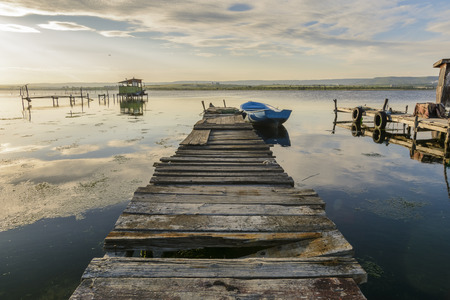 Wooden pier on a lake with a fishing hut. sunset with calm water Stock Photo