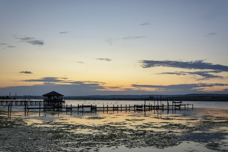 wooden Fishing hut in a lake with pier and fishing net at sunset