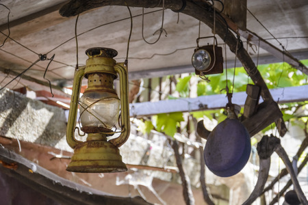 old rusty petrol lantern suspended on a wood piece