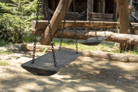 wooden swing in the middle of a forest.