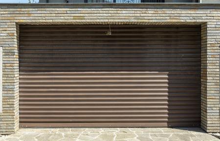 Iron garage door with stone bricks on the side.big shadow
