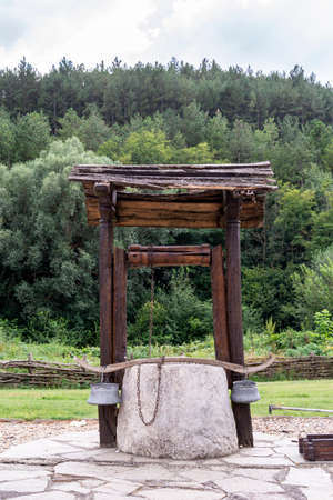 Wooden hand made well in a garden against a forest.
