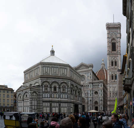 Firenze, Italy, April 26, 2019: Tourist on the top of the cathedral Le Duomo, Santa Maria del Fiore visiting and taking panoramic photos