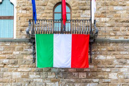 tree flags on a balcony, the italian flag, the firenze blazon ans European flag.