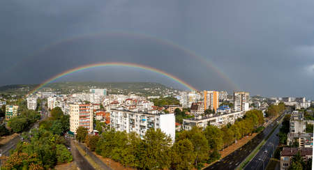 Panoramic shot of a double rainbow with Halo over the city of Varna