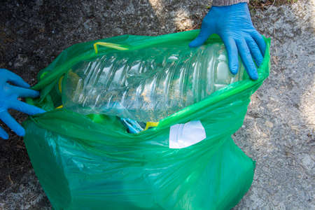 Plastic bottle in a green plastic bag, blank place for text and advertising Stok Fotoğraf