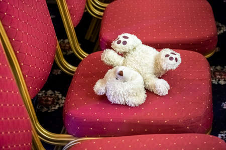 white teddy bear forgotten on a red chair.
