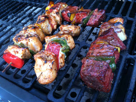 grill: Skewered chicken and beef on the grill.