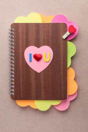 Wood cut alphabets and small red heart placed on top of wooden cover book with multi-colored heart shaped posted notes and small wooden clip with red heart design, perfect for using as template for Valentine or love card Banco de Imagens