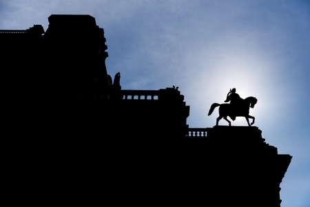silueta hombre: Silueta del hombre en la estatua del caballo en la parte superior de un edificio de Viena con el sol directamente detr�s, cielo azul con nubes poco esponjosas en el fondo