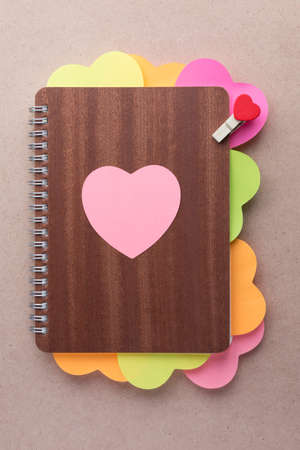 posted: Wooden cover book with multi-colored heart shaped posted notes and small wooden clip with red heart design, perfect for using as template for Valentine or love card