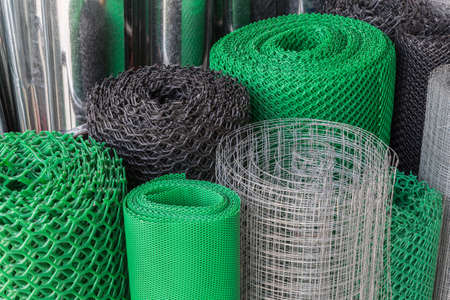 iron fence: Rolls of plastice and steel wire mesh in various sizes and patterns Stock Photo