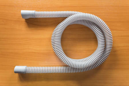 apnea: CPAP air hose on wooden table, use with CPAP machine and mask to help patients with sleep apnea problem