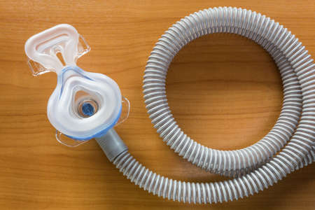 machine: CPAP mask attaching to the air hose , use with CPAP machine to help patients with sleep apnea problem, showing the inside side of the mask, displaying on wooden table