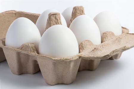 Zes witte eieren in gerecycleerde pakpapiercontainer op witte achtergrond Stockfoto