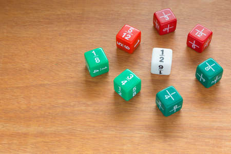 Three color fraction dices, use in elementary classrooms for students to learn about math fractions Stock Photo