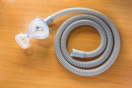 apnea: CPAP hose and mask on wood table, for people with sleep apnea