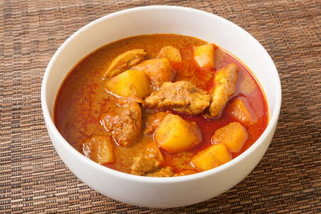 Spicy Thai red chicken curry, called Massaman curry, in white bowl sitting on bamboo mat