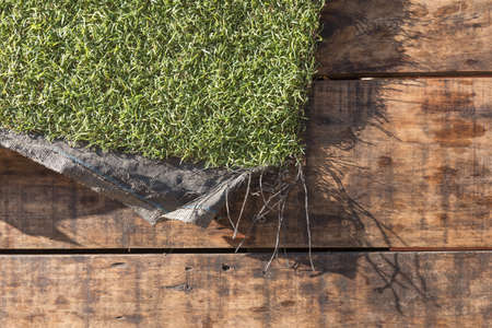 wood grass: Piece of artificial grass mat hanging over weathered rustic wood panels on a sunny day