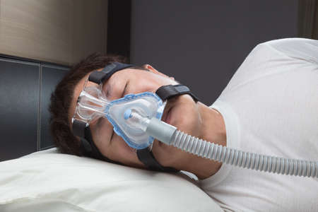 snore: Asian man with sleep apnea using CPAP machine, wearing headgear mask connecting to air tube