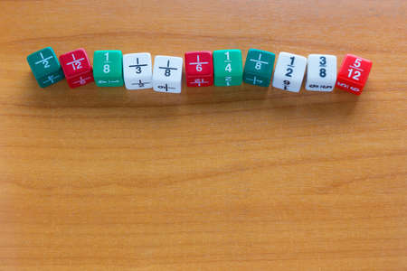 fraction: Multicolored fraction dices line up on wooden table with room for copyspace at bottom of frame