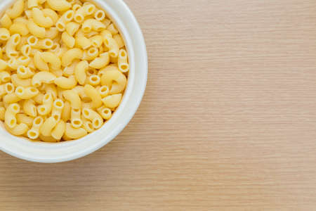 room for copy: Macaroni in white bowl on wooden table, compose to the side to leave room for copy space