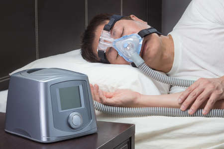 Asian man with sleep apnea using CPAP machine, wearing headgear mask connecting to air tube