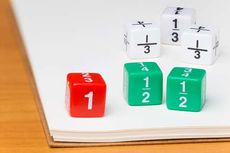 Colored fraction dices on blank white paper notebook on wooden desk, selective focus on dices
