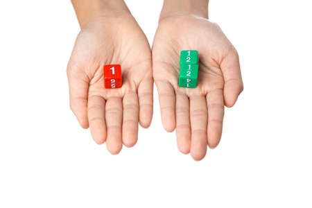 Two hands holding fraction dices, one hand with one red dice showing number one, the other hand with two green dices showing one half numbers, selective focus on dices, on white background