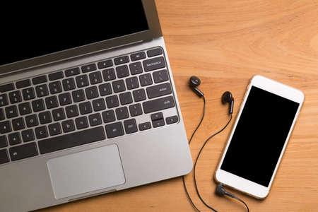 Portable computer laptop, smartphone, earphones, on wood table Stock Photo