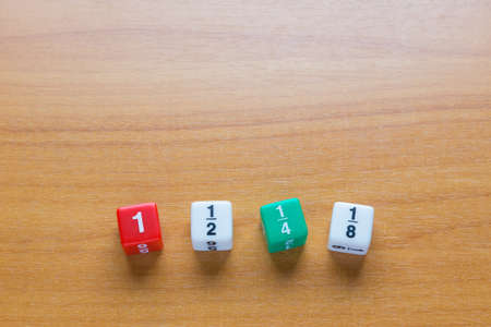 fraction: Four color fraction dices, 1, 12, 14, and 18, on wooden table, selective focus on dices Stock Photo