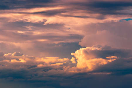 enhanced: Orange fluffy patches of clouds against deep blue sky at sunset, color enhanced Stock Photo