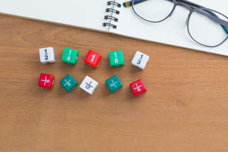 fraction: Color fraction dices, blank white notebook on wooden desk, with copyspace for text