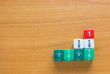fraction: Color fraction dices; whole number, half, and quarters on wood table, with room for copyspace
