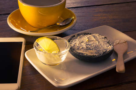 spreaded: Half charcoal bagel with spreaded cream cheese on white plate, cream cheese in clear cup with a slice of lemon, empty coffee cup with silver spoon, cell phone, all on wooden table, in two tone dramatic morning light Stock Photo