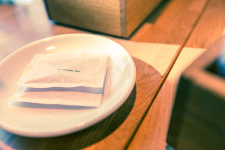 cinematic: Two white sugar bags with small black text, on white plate, on wooden table in morning light, selective focus on the letters with shallow depth of field, color effect treatment in post for cinematic look Stock Photo