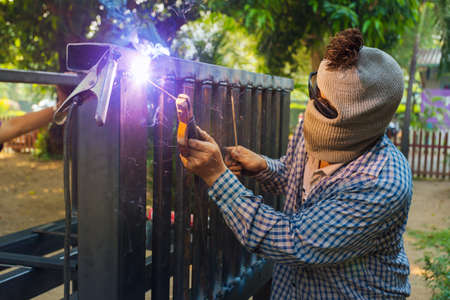 blurr: Unidentified hooded man welding steel platform, bright light and sparks, outdoor with blurr background trees