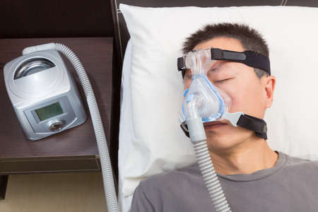 Asian man with sleep apnea using CPAP machine, wearing headgear mask connecting to air tube, selective focus on the man and headgear mask
