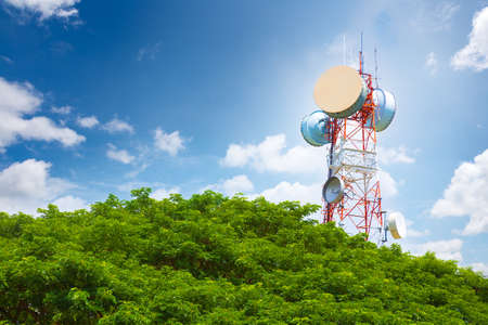 peaking: Telecommunication tower peaking above tree top on a bright blue sunny sky and white fluffy clouds Stock Photo